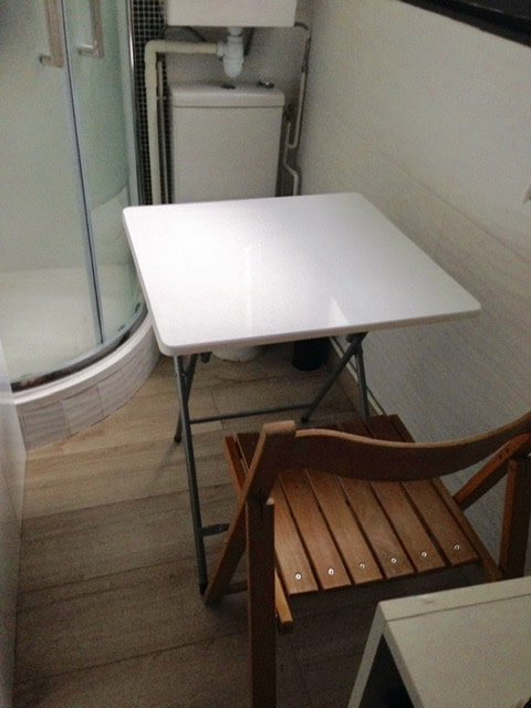 A foldable table and chair set in front of a shower stall and toilet