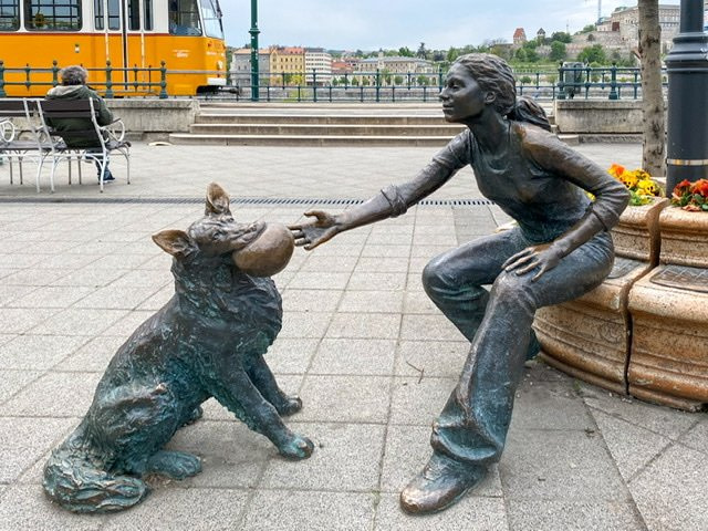 Statue of a girl reaching for a ball in a dog's mouth