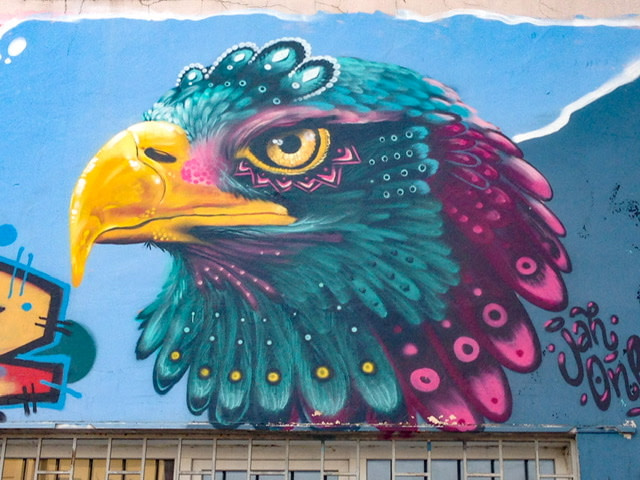 Mural of an eagle in bright yellow, teal, and magenta