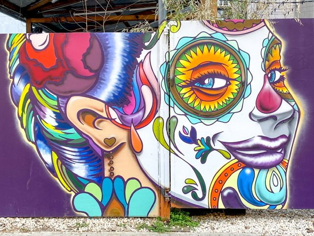 A large mural of a colorfully decorated face