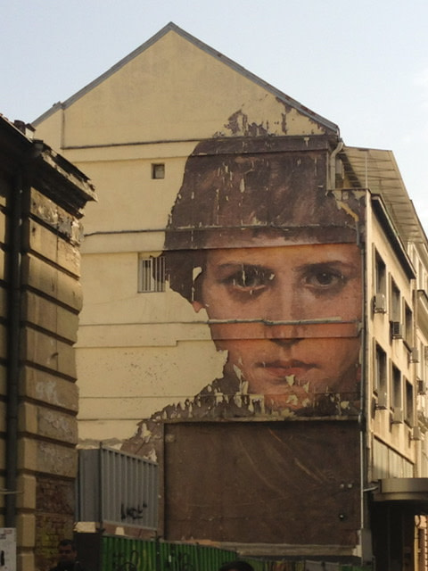 Mural on a serious-looking boy on a yellow building
