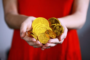 Midsection of a woman in a red dress holding gold coins