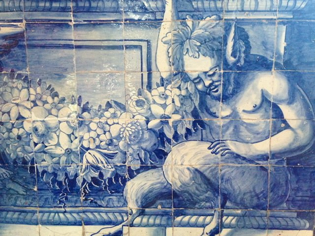 A close up of azulejo tiles featuring a faun and flowers