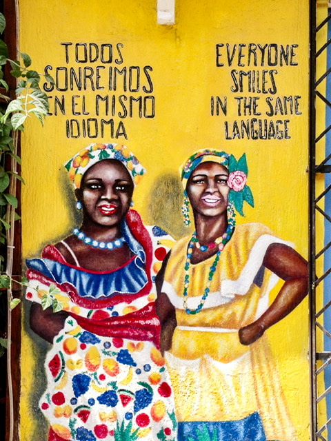 "Mural of two women with the sentiment ""everyone smiles in the same language"""