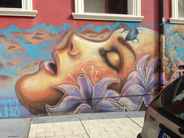 Mural of a woman's face in profile with light purple flowers