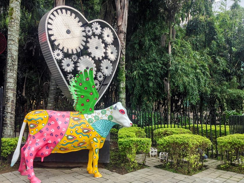 A colorful cow statue with lush vegetation